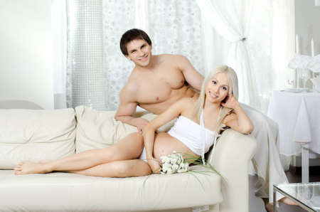 young pregnant woman with husband  on white sofa in light home room photo