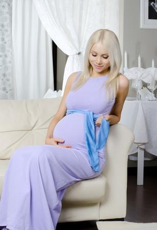 pregnant underwear: joven mujer embarazada se siente con las flores en la cama en la habitaci�n de su casa blanca