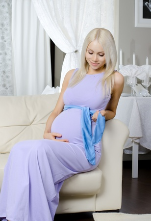 blonde underwear: young pregnant woman sit with flowers on white bed in home room Stock Photo