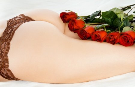 The bouquet of red and white roses lays between beautiful, young, harmonous female legs Stock Photo - 12773474
