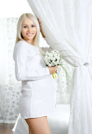 young pregnant woman with flowers, in  light bedroom photo