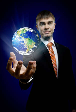 businessman hold in hand terrestrial globe, on dark blue background,  business conceptimage planet by: Stokli, Nelson, Hasler Laboratory for Atmospheres Goddard Space Flight Center www.rsd.gsfc.nasa.gov/rsd Stock Photo - 12773277