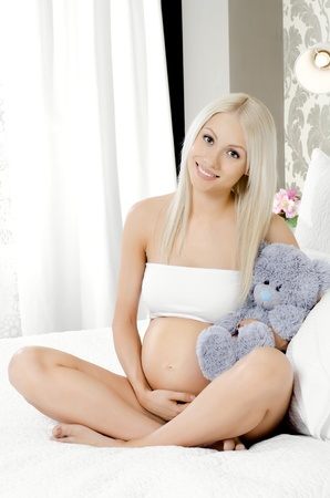 fetation: young pregnant woman sit with flowers on white bed in light  home bedroom