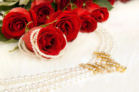 rose photo: Bouquet beautiful red roses and pearl necklace; lay on white to fur