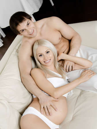 fetation: young pregnant woman with husband  on white sofa in light bedroom