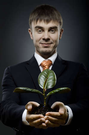 portrait  the  beautiful  businessman in black costume with  scion  rubber plant Stock Photo - 12773784
