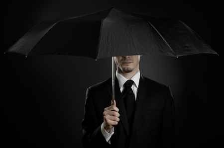 espionage: portrait  man the  beautiful  man in black costume with blak umbrella,  special-service agent or  body guard