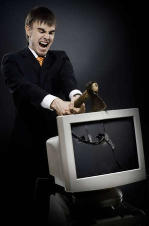 frenzy businessman chop-down old monitor on dark grey background photo