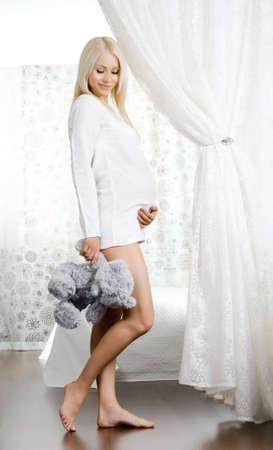 pregnant underwear: joven mujer embarazada con el juguete, en el dormitorio de la luz