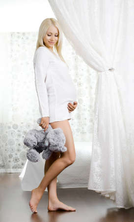 fetation: young pregnant woman with toy, in  light bedroom