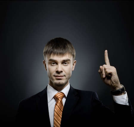 handsome businessman index finger point upwards, on dark grey background Stock Photo - 12773974