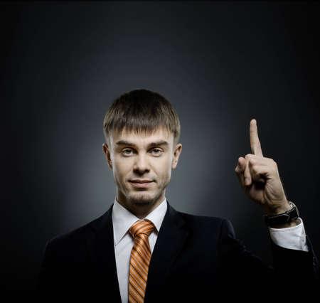 handsome businessman index finger point upwards, on dark grey background Stock Photo - 12773974
