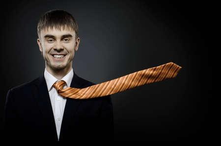 portrait  the  beautiful  businessman careerist in black costume and orange necktie photo