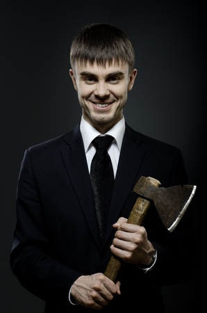 angry businessman: portrait  the  beautiful  businessman  in black costume and black necktie with axe, sinister look and smile Stock Photo