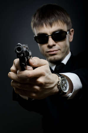 stringent: portrait  the  beautiful  man in black costume,  special-service agent or  body guard with  pistol Stock Photo