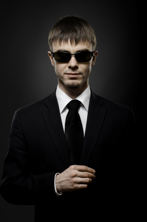 portrait  the  beautiful  man in black costume,  special-service agent or  body guard photo