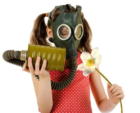 niña en máscara de gas, huele a flor blanca grande, sobre fondo blanco, aislados Foto de archivo