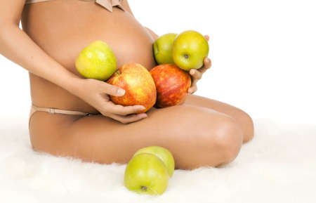 expectant mother: body pregnant woman with very big stomach, hand hold apple, on white background, isolated