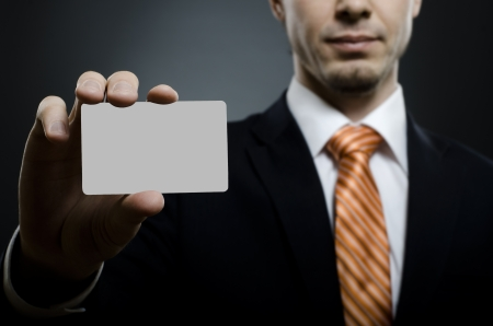 business card in hand: businessman in black costume and orange necktie reach out on camera and show credit card or visiting card, close up
