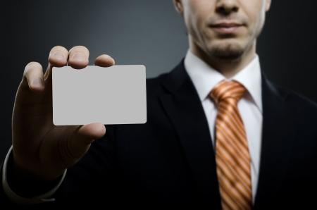 hand business card: uomo d'affari in costume nero e arancione cravatta raggiungere sulla macchina fotografica e mostrare carta di credito o biglietto da visita, close up Archivio Fotografico