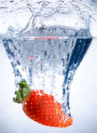 one red beauty big  strawberry  drop in blue water with splashes photo