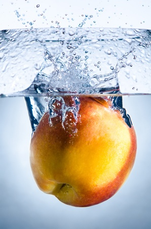 plunge: one yellow peach big  strawberry  drop in blue water with splashes Stock Photo