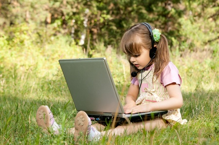 i net: The small beautiful girl works on a computer, sits on a  green lawn