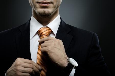 галстук: портрет красивый бизнесмен в черный костюм Привяжите один Фото со стока