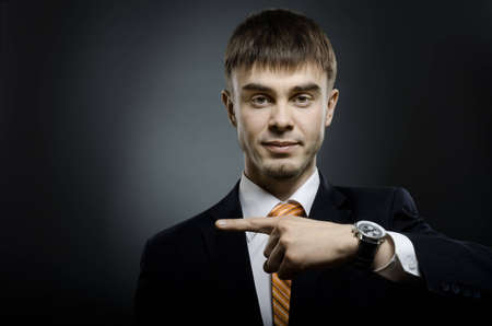 businessman index finger point sideways, on dark grey background, horizontal photo Stock Photo - 12773907