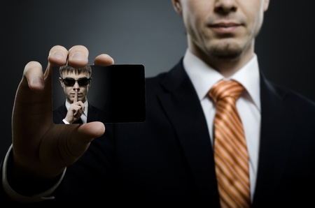 silently: secret agent in black costume and orange necktie reach out on camera and show  visiting card, close up