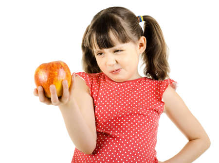 disobedient child: disobedient little girl hold apple and make displeased  grimace, on white background, isolated