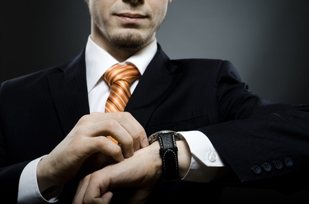 businessman in black costume wind clock  wristwatch  on hand,  close up