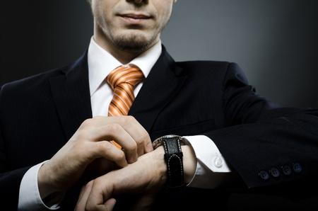business costume: businessman in black costume wind clock  wristwatch  on hand,  close up