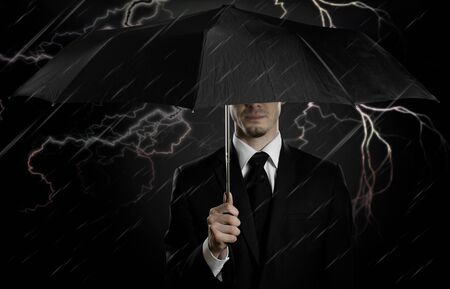 undercover agent: portrait  man the  beautiful  man in black costume with blak umbrella,  special-service agent or  guard Stock Photo