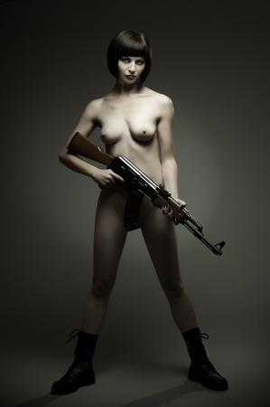 girl sexy nude: la sensualidad hermosa chica sexy desnuda con metralleta, sobre un fondo oscuro la luz glamour, Foto de archivo