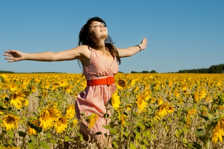 develop: The young beautiful woman quickly runs on a glade of sunflower, smiles, hands are opened  Stock Photo
