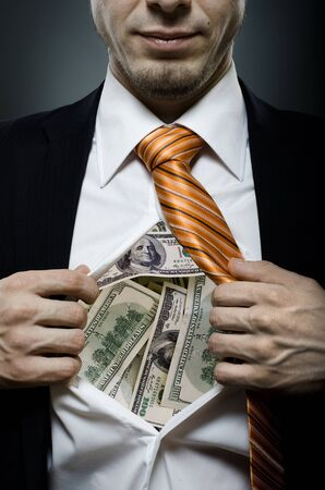 venality businessman or banker  in black costume throw open ones shirt packed heap dollars  Stock Photo