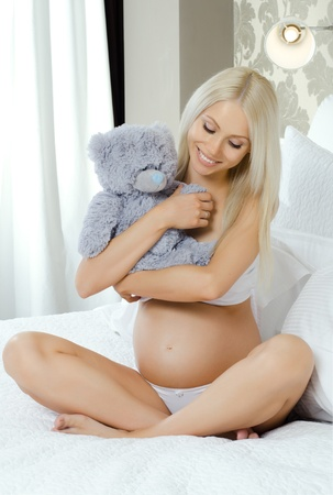 young pregnant woman with toy, in  light bedroom Stock Photo - 12921735