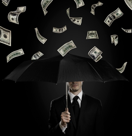 downfall: man in black costume with blak umbrella under rain of  currency note,  concept economics  crisis