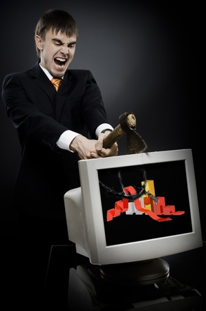 disruption: frenzy businessman chop-down old monitor on dark grey background, concept economics  crisis