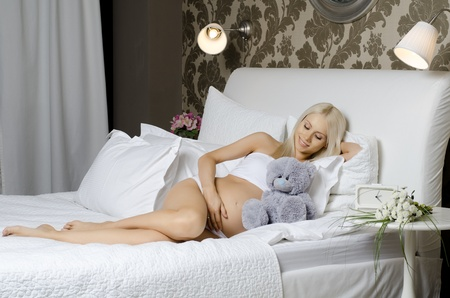 young beauty pregnant  happiness woman with toy, in  bedroom photo