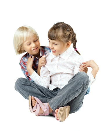 child couple: two  little children sitting embrace and smile, on white background, isolated Stock Photo