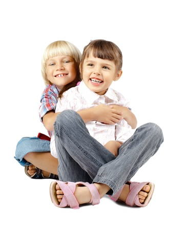 romp: two  little children sitting embrace and smile, on white background, isolated Stock Photo