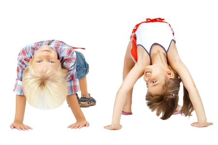 romp: little children  stand head over heels and smile, on white background, isolated