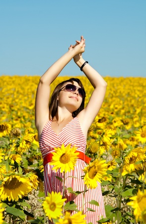 The young beautiful woman quickly stand  on a glade of sunflower, smiles photo