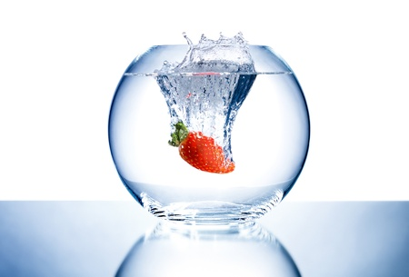 crystal clear: one red beauty big  strawberry  drop in blue water with splashes; on white background, isolated