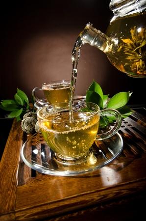pellucid: foto vertical, del t� de flujo de vidrio tetera verde en la taza sobre fondo marr�n, ceremonia del t�