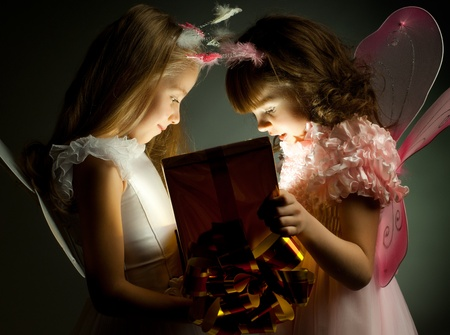 kids dress: two little girl examine gift in fancy box, smile, on dark background