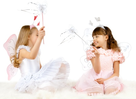 two beautiful  little girl with wings, sit and  fun game, smile,  on white background, isolated Stock Photo - 13205309