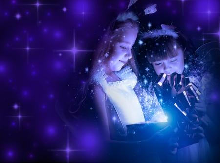 fancy box: two little girl examine gift in fancy box, smile, on dark blue background Stock Photo